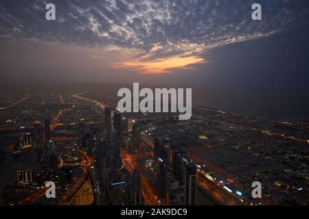 DUBAI, UNITED ARAB EMIRATES - NOVEMBER 19, 2019: Dubai illuminated city high angle view with skyscrapers in a cloudy evening
