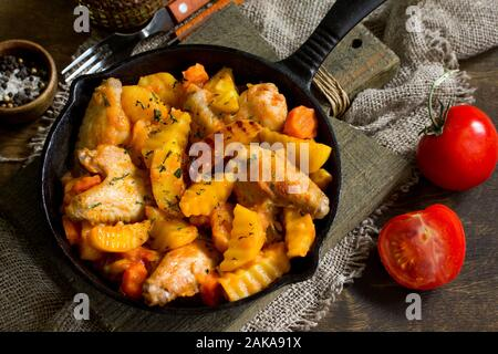 Thanksgiving dinner. Stewed potatoes with chicken wings, tomatoes and spices, served in a cast-iron frying pan on a rustic table. - Stock Photo