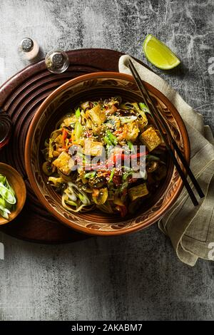 Asian vegan stir fry with tofu, rice noodles and vegetables, top view. - Stock Photo