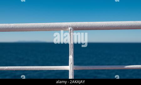 White protective handrail of a ferry boat sailing at sea - Stock Photo