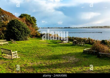 Colour landscape photograph looking over harbour from viewpoint with pier and Sandbank's millionaires row in distance, taken on Evening hill, Poole - Stock Photo