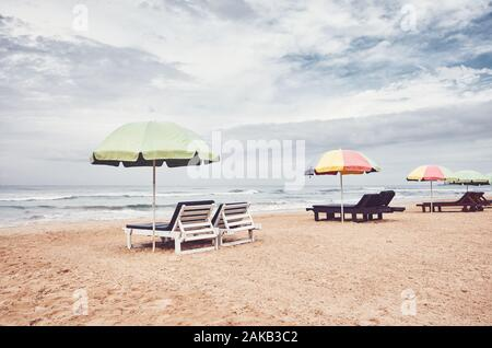 Sunbeds with umbrellas on an empty beach, color toning applied, Sri Lanka. - Stock Photo