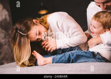 Happy family having fun lying down on bed at home. Happy Family In Bed. Mom dad and son lie on bedroom at within doors. father, mother and child - Stock Photo