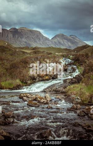 Waterfalls of Abhainn Gleann Leireag with Quinag in the background - Stock Photo