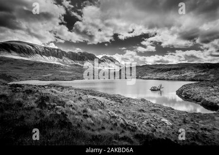 The locan of Loch Uidh na a-larna with Quinag in the background - Stock Photo