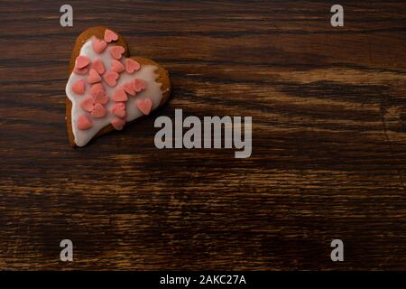 one homemade heart-shaped gingerbread with white icing and colorful sugar decoration on the background of an old wooden table - Stock Photo