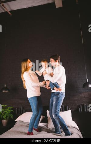 Family Jumping On Bed Together. Family fun. The beautiful family jumping on the bed. Caucasian mom dad and son active evening vacation at home, fun - Stock Photo