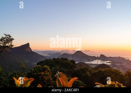 Sunrise over the city of Rio de Janeiro,Sugarloaf and Christ the Redeemer statue from Vista Chinesa. - Stock Photo