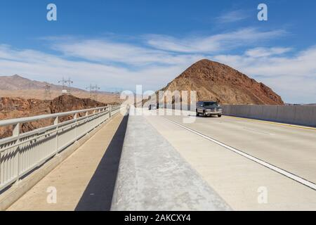 Boulder City, Nevada, USA- 01 June 2015: Cars on the highway over Hoover Dam on the Colorado River. High voltage poles and hills in the background. - Stock Photo