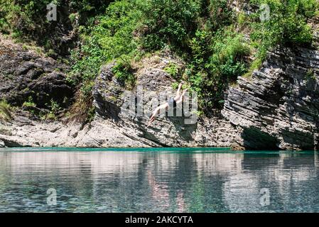 A man jumps from a cliff into a river. The abundance of nature. Albanian rivers.Cliff jumping into a mountain river . - Stock Photo