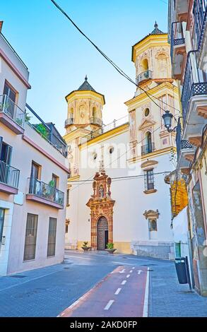 The modest facade of San Felipe Neri Parish Church with two bell towers and beautiful carved door frame, Malaga, Spain Stock Photo