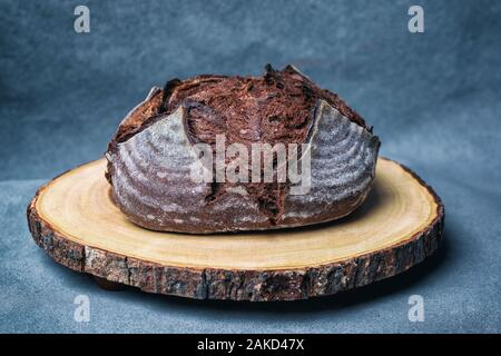 Artisan loaf of traditional Homemade Chocolate Pumpernickel sourdough Boule bread with crust on a wooden cut log board - Stock Photo