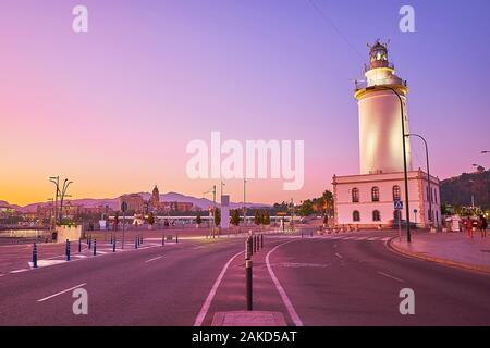 Walk La Farola promenade and enjoy the evening view of Malaga lighthouse (faro), located at the entrance to the port, Spain - Stock Photo