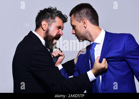 Coworkers decide upon best working position. Businessmen with angry faces in formal suits on grey background. Company leaders fight for business leadership. Business opposition and competition concept - Stock Photo