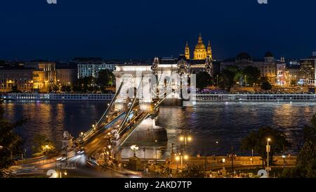Night view of architectural landmarks Saint Stephens Basilica and Szechenyi Chain Bridge over the Danube River in Budapest, Hungary.