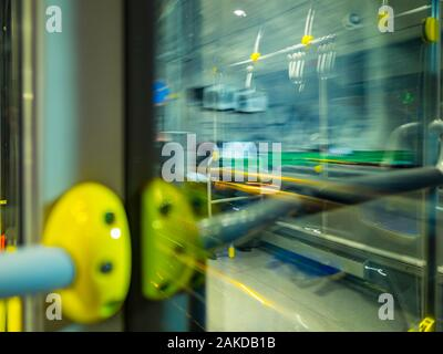 Passenger view from bus through window city town urban street motion moving driving intentionally blurry blur background - Stock Photo