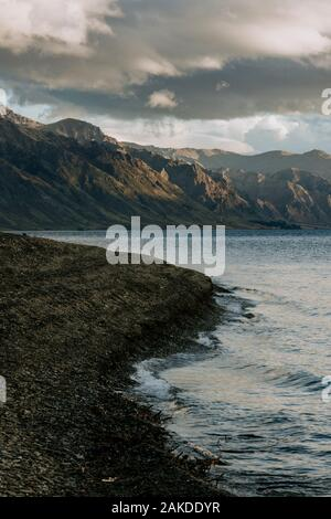 view of sunset over jagged mountains from beach next to Lake Hawea - Stock Photo