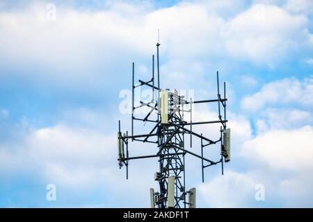 A low angle close up shot of a cell site tower, lattice design, housing cellular network antennae against a light blue cloudy sky with copy space - Stock Photo