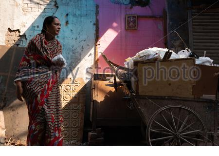 Indian woman in colorful saree walks by a pink and blue wall in the Old Delhi neighborhood of New Delhi, India. - Stock Photo