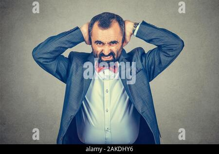 Closeup portrait adult angry bearded man in elegant jacket with red bow tie stressed hands on head covering his ears isolated gray wall background tel - Stock Photo