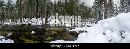 Merced River Runs Through Snowy Forest in Yosemite - Stock Photo