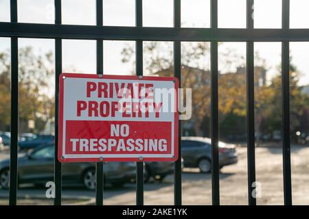 Private property no trespassing sign on black gate in front of parking lot - Stock Photo