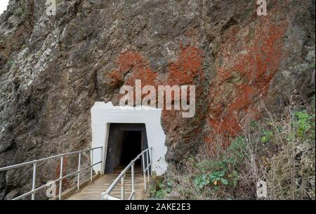 Walking path leading into mountain side tunnel covered in rust - Stock Photo