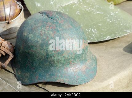 Rusty and holed military helmet, found on the locations of past battles - Stock Photo