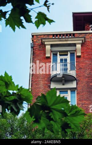 Low angle view of a balcony on a beautiful residential building with red brick framed by tree branches and green leaves.