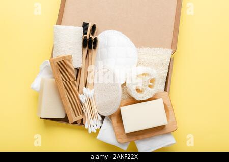 Zero waste with natural self care accessories on yellow. Bamboo toothbrushes, handmade soap shampoo bars, cotton buds pads, hygiene products luffa, top view, selective focus - Stock Photo