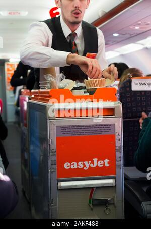 Cabin crew / air steward serves drinks and snacks to passengers from a trolley cart during an Easyjet flight on an Airbus aircraft plane. (115)