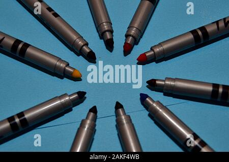 Coloured markers of various colours forming a circle on a blue background - Stock Photo