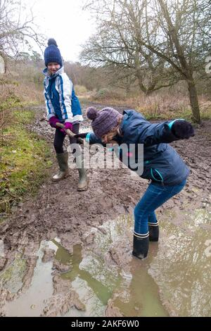 Two young girls / girl / sisters aged nine and age 7, wearing Wellington boots, enjoys helping, rescuing, and playing in a big wet muddy puddle during a family walk over West End Common, Esher, Surrey. UK (115) - Stock Photo
