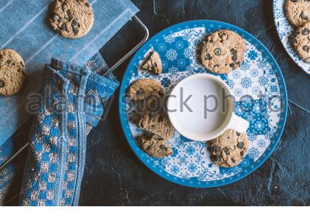 Flat lay of some cookies and milk on a chalk board - Stock Photo