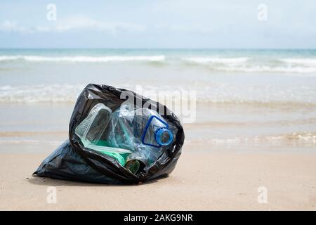 closeup of a gray plastic bag with collected garbage on the sand of a lonely beach,  next to the water, in the background - Stock Photo