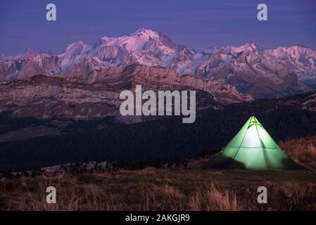 France, Haute Savoie, Bornes massif, Glieres, itinerant trek day 1, bivouac under tent at the top of Parmelan with view towards the Mont Blanc massif at dusk - Stock Photo