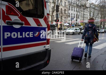 French Police Van and Cordon block road to traffic in anticipation of demonstrations in protest of government pension reforms, as woman walks through barrier with suitcase, travel disruption during strike (la grève), boulevard Barbès (near gare du nord train station), 75018, Paris, France, 9th January 2020 - Stock Photo