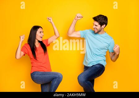 Photo of funny two people guy lady celebrating favorite football team winning raising fists rejoicing wear casual blue orange t-shirts jeans isolated - Stock Photo