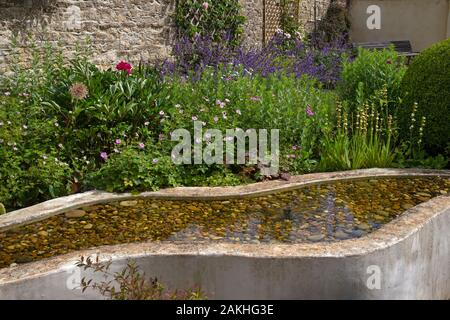Raised shallow pond water feature in english garden - Stock Photo