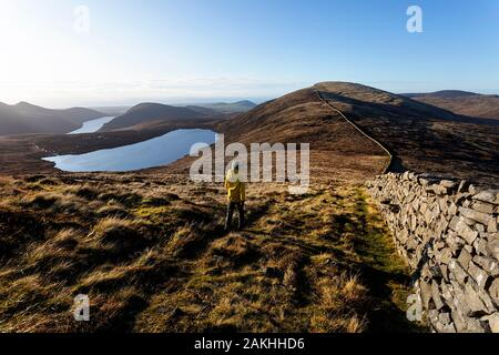 Mourne Mountains and lakes in Northern Ireland, UK. View from the peak of Slieve Loughshannagh, young boy walking by the stone wall - Stock Photo