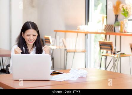 Beautiful asian young woman working online on laptop sitting at coffee shop, professional female freelancer with paper crumpled and using notebook com - Stock Photo