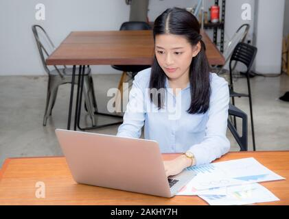 Beautiful of portrait asian young woman working with graph statistic paper on laptop sitting at coffee shop, professional female freelancer using note - Stock Photo