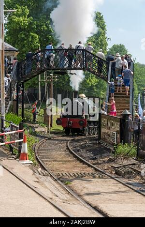 A steam train approaching the station and footbridge as part of the Fawley Hill Steam and Vintage Transport Weekend at Lord McAlpine's private railway - Stock Photo