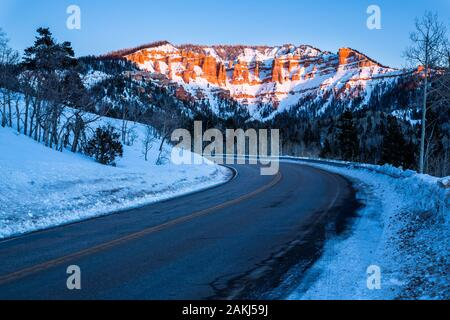 Road traveling toward desert sandstone formations near Bryce Canyon and Cedar Breaks in Southern Utah desert. Snow covers the ground and pink light of - Stock Photo