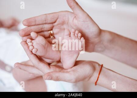 Baby feet in mother hands. Tiny Newborn Baby's feet on female Shaped hands closeup. Mom and her Child. Happy Family concept. Beautiful conceptual imag - Stock Photo