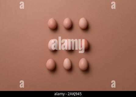 Eggs aligned on a brown paper background. Above view of organic brown eggs in a matrix displayed. Freshly collected eggs. Minimal image of eggs. - Stock Photo