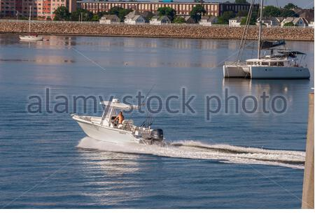 New Bedford, Massachusetts, USA - July 26, 2019: Recreational fisherman accelerating away from hurricane barrier on nice morning - Stock Photo