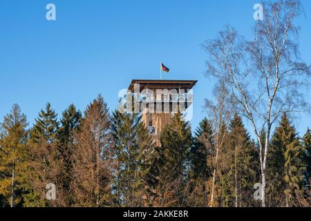 Luneberg, Germany - Nov 10, 2019: Tourists up on the overlook tower in Heide Wildlife Park with German flag on top - Stock Photo