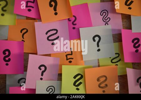 Handwritten different question marks on red, pink, white, yellow and orange sticky notes - Stock Photo