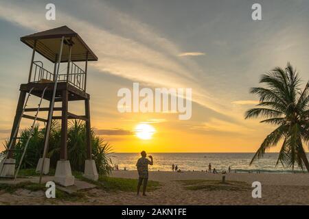 a man walking and take photo around lifegaurd tower during sunset at Karon beach Phuket - Stock Photo